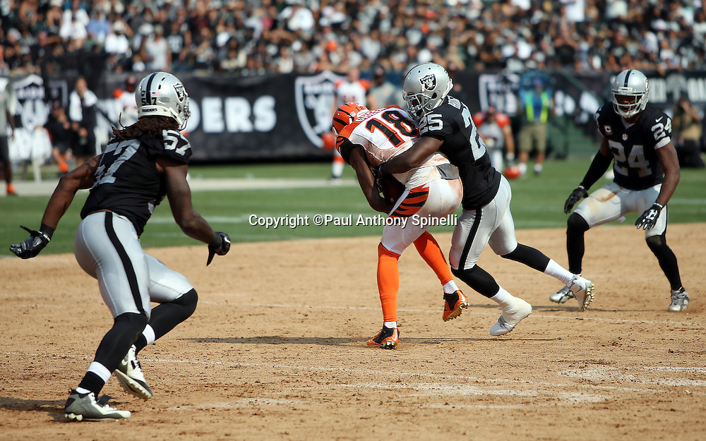 Cincinnati Bengals wide receiver A.J. Green (18) catches a third quarter pass and gets tackled by Oakland Raiders cornerback D.J. Hayden (25) during the 2015 NFL week 1 regular season football game against the Oakland Raiders on Sunday, Sept. 13, 2015 in Oakland, Calif. The Bengals won the game 33-13. (©Paul Anthony Spinelli)