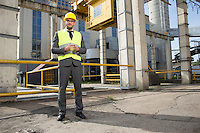 Full length portrait of confident young male architect standing outside industry
