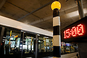 Passing bus and passenger inside with beletia beacon and current time of three o'clock in bus station at Heathrow's terminal 5.