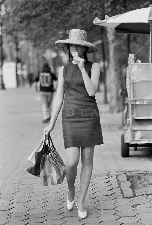 Woman in New York City eating an ice cream and walking on the street
