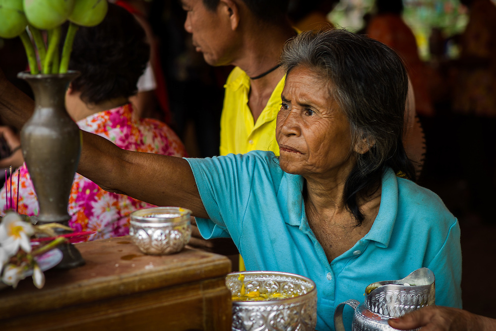 A woman prays by lighting candles at  a Songkran festival in Nakhon Nayok, Thailand.