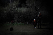 Refugees from Afghanistan and Syria wait to be transfer to a camp for the night after they arrived at night with a rubber boat on the shores of Lesbos near Skala Sikaminias,<br /> Greece on 03 November, 2015. Lesbos, the Greek vacation island in the Aegean Sea between Turkey and Greece, faces massive refugee flows from the Middle East countries.