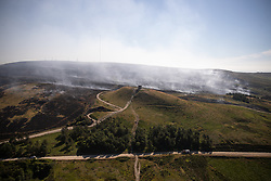 © Licensed to London News Pictures . 04/07/2018 . Bolton , UK . Free to use aerial photograph provided by the Woodland Trust showing the scarred landscape at Winter Hill behind the historic Rivington Pike beacon , as fire-fighters continue to work to control the spread of the blaze . The Woodland Trust estimates it has lost a fifth of the area it manages around Winter Hill , damaging precious moors and upland grassland , endangering the surrounding woods and wildlife and threatening people's homes . Photo credit: Joel Goodman/LNP