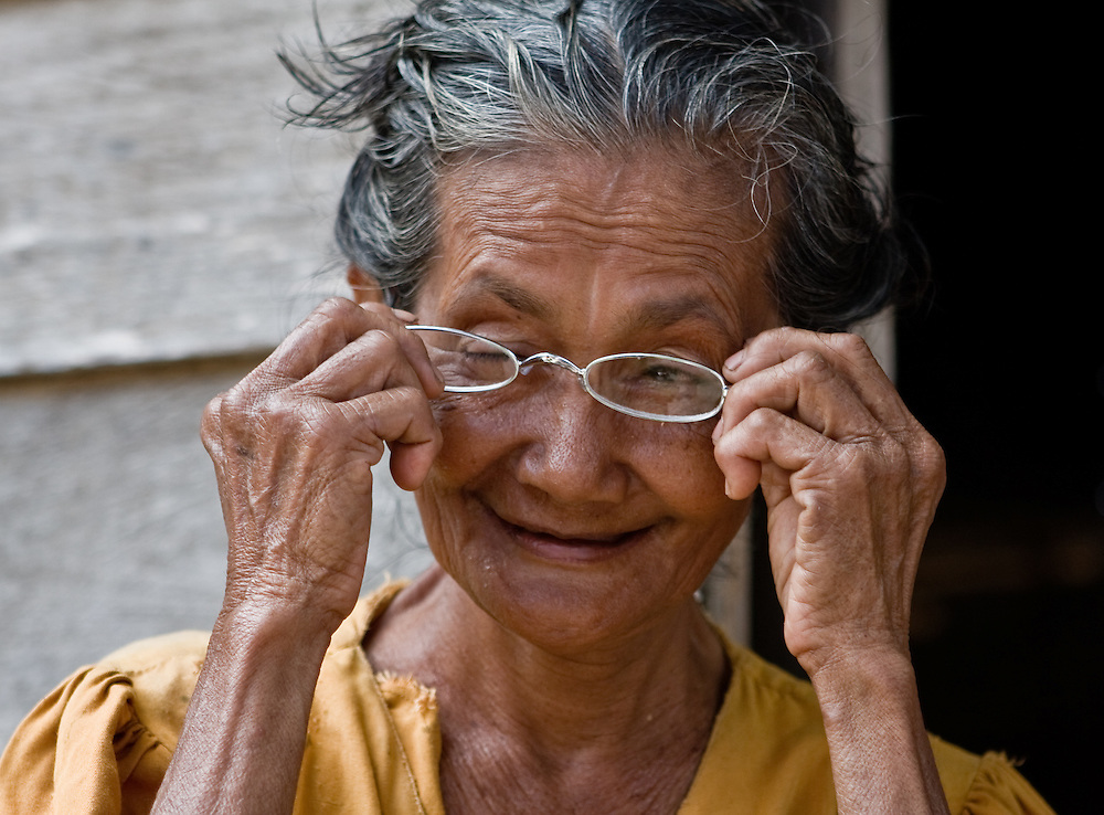 An elderly woman tries on new reading glasses in Central Sulawesi