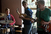 A teenage band of drums, bass and lead guitar perform in front of parents in an upstairs pub room in south London. 15 year-old lads play their own songs and covers by other musical artists.