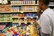 (MODEL RELEASED IMAGE). Shopping for one weeks' worth of food, Brandon contemplates which flavors of Kool-Aid to select for the upcoming photo shoot. (Supporting image from the project Hungry Planet: What the World Eats.) The Revis family of Raleigh, North Carolina, is one of the thirty families featured, with a weeks' worth of food, in the book Hungry Planet: What the World Eats.