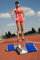 Starting block with Female track athlete standing in background