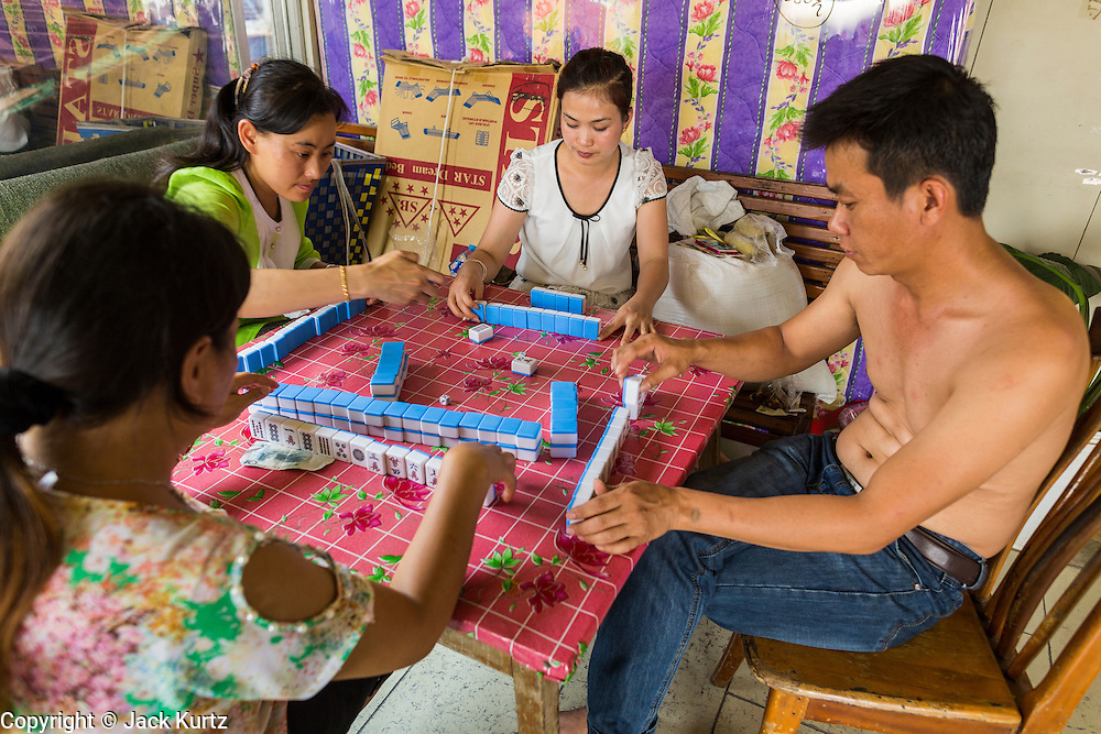 24 APRIL 2014 - CHIANG SAEN, CHIANG RAI, THAILAND: Passengers on a Chinese cargo boat, carrying taking cars, Red Bull energy drink and passengers Kunming in China play mahjong. Chinese businesses play an increasingly important role in the Chiang Rai economy. Consumer goods made in China are shipped to Thailand while agricultural products made in Thailand are shipped to China. Large Chinese cargo boats ply the Mekong River as far south as Chiang Saen in the dry season and Chiang Khong when river levels go up in the rainy season.    PHOTO BY JACK KURTZ