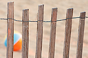 Picture of a beach ball taken through   sand fence along the beaches of the Outer Banks.