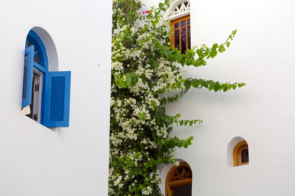 Decorative Moroccan window shutter, Asilah, Northern Morocco, 2015-08-10.<br /><br />Asilah is a sleepy fishing town in the North of Morocco, just one hour south of Tangier. While not completely off Morocco's well-beaten path, it's often missed by travellers bound inland for Fez or Chefchaouen, yet has a uniquely alluring charm. With an immaculately restored medina that's re-painted vivid shades of blue & white each summer, Asilah has the feel of being Morocco's own Santorini - a great spot to see the more chilled out, seaside town life in Morocco.  <br /><br />The town lies in the middle of a fascinating history in historical, architectural and artistic terms. It's 3,600 year old history that includes a varied range of occupiers, involving Roman, Arab Portuguese, Spanish and French colonisation. Many famous writers and artists have spent time here; in ancient times is it reported Herecules did a tour of the area and, more recently; Paul Bowles, Tennessee Williams, Edith Wharton, Jean Genet (who is buried in the nearby town of Larache), William Burroughs, Jimi Hendrix and Henri Matisse have all found the area inspiring. The Portuguese ramparts remain fully intact and a full day can be spent wandering through its old gates and the ever narrowing medina streets inside the walls.<br /><br />The architecture in Asilah has been heavily influenced by these different periods of occupation, which is one of the main reasons for its unique and characterful feel. Evidence of Mediterranean design can be seen in the rampart walls and gates themselves, reflecting the Spanish & Portuguese influence on the Asilah's development, Roman ruins can be found in the nearby town of Larache and Arab influences are more subtly found in the decorative window shutters and the labyrinth like medina layout to the streets. <br /><br />If a lover of the quirkier details found in the medinas of Morocco, then Asilah won't disappoint, with hundreds of creatively designed doorways, decorative window s