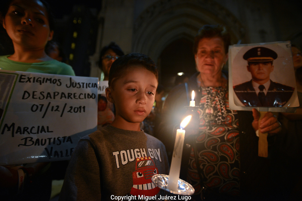 NEW YORK, NY - SEPT 08, 2012 -  Brandon C. Peluffo, 7, joined his grandmother, Maria Guadalupe Guzman (R) and other relatives holding a candlelight vigil in Harlem September 6, to remember sons, uncles, fathers and other loved ones killed in Mexico's drug war. Guzman holds a photo of her son, Lt. Miguel Orlando  Muñoz--Brandon's uncle--whose disappearance she blames on corrupt members of the Mexican Army. The vigil is part of the Caravan for Peace with Justice, which has traveled across the U.S. this summer to draw attention to what they consider failed U.S. and Mexican policies fueling Mexico's drug war, which has left more than 60,000 people dead or missing.(PHOTO: MIGUEL JUAREZ LUGO)