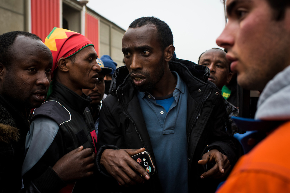 Refugees discuss their eventual destination with personnel supervising their boarding of a bus at a relocation center near The Jungle refugee camp on October 24, 2016 in Calais, France.