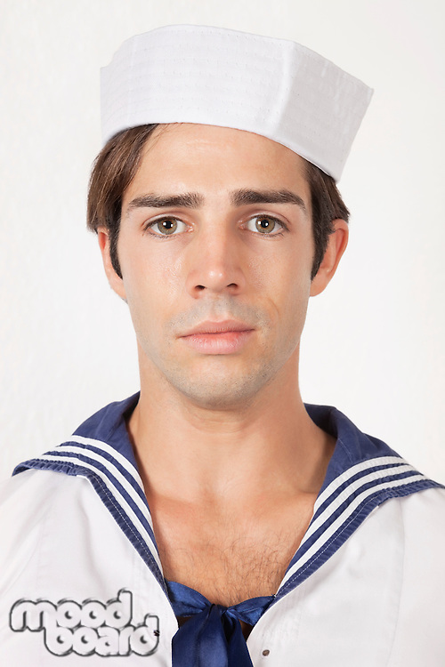 Portrait of sad young man in sailor's uniform against gray background