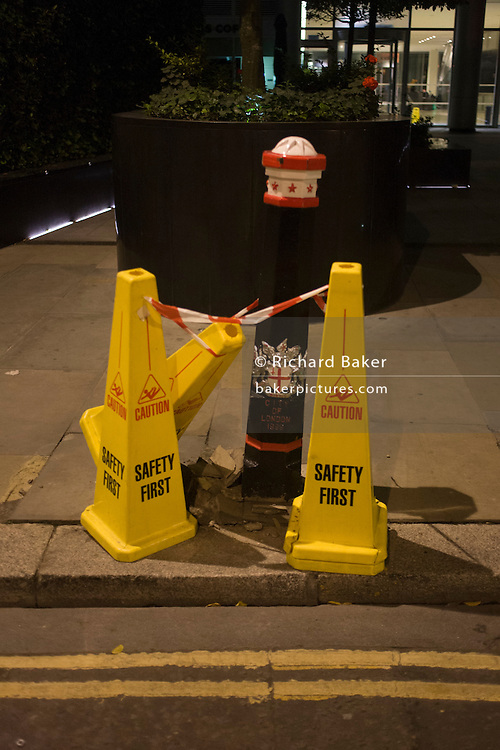 Health and Safety cones, taping off a broken City of London bollard.