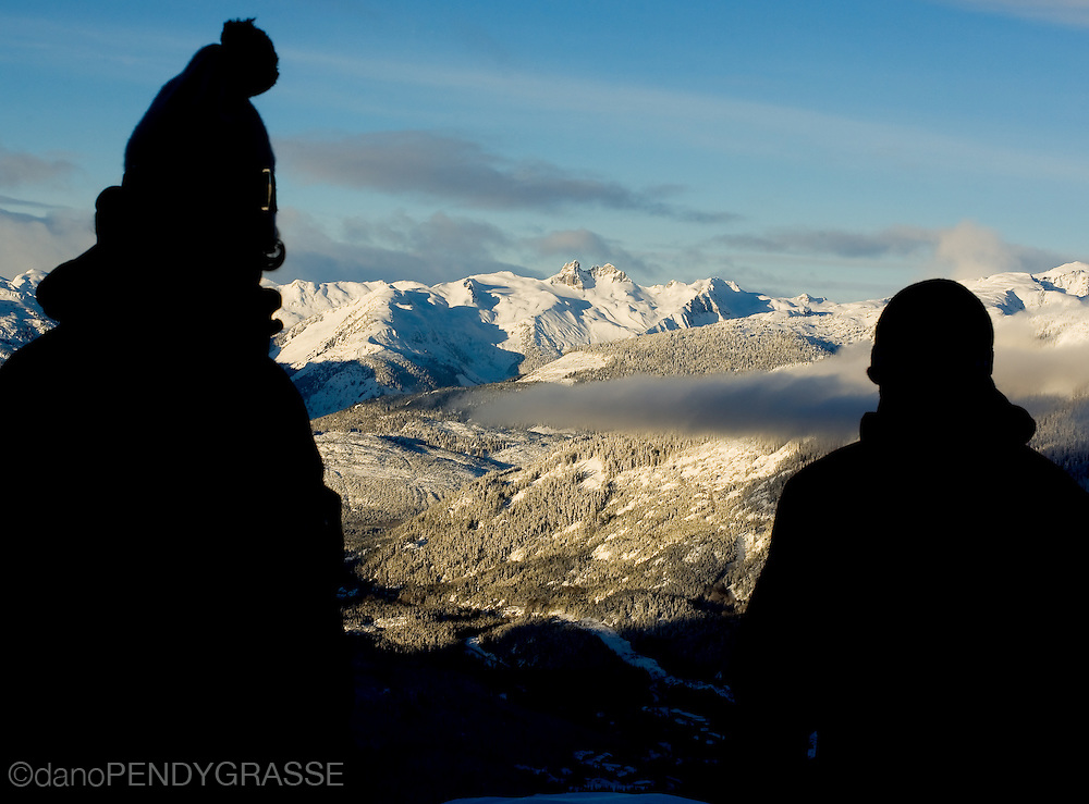 Two men look out into the beautiful morning light over the Coast Mountains, British Columbia.