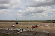Beachcombers explore pools at low-tide on the estuary at Wells-next-the-Sea in Nofolk.