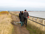 View from behind of people wearing winter coats walking on path by North Sea coast, Bawdsey, Suffolk, England, UK