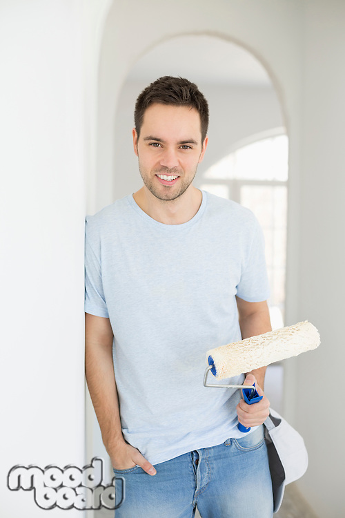Portrait of handsome man holding paint roller in new house