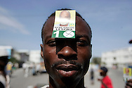 A Haitian man holds up a card with the face of Presidential candidate Rene Preval  at a in a rally in the Cite-Soliel neighborhood of Port-Au-Prince, Haiti February 1, 2006. Demonstrators were protesting the United Nations' plans to have voting stations for voters outside of Cite-Soliel due to security concerns...Photo by Keith Bedford