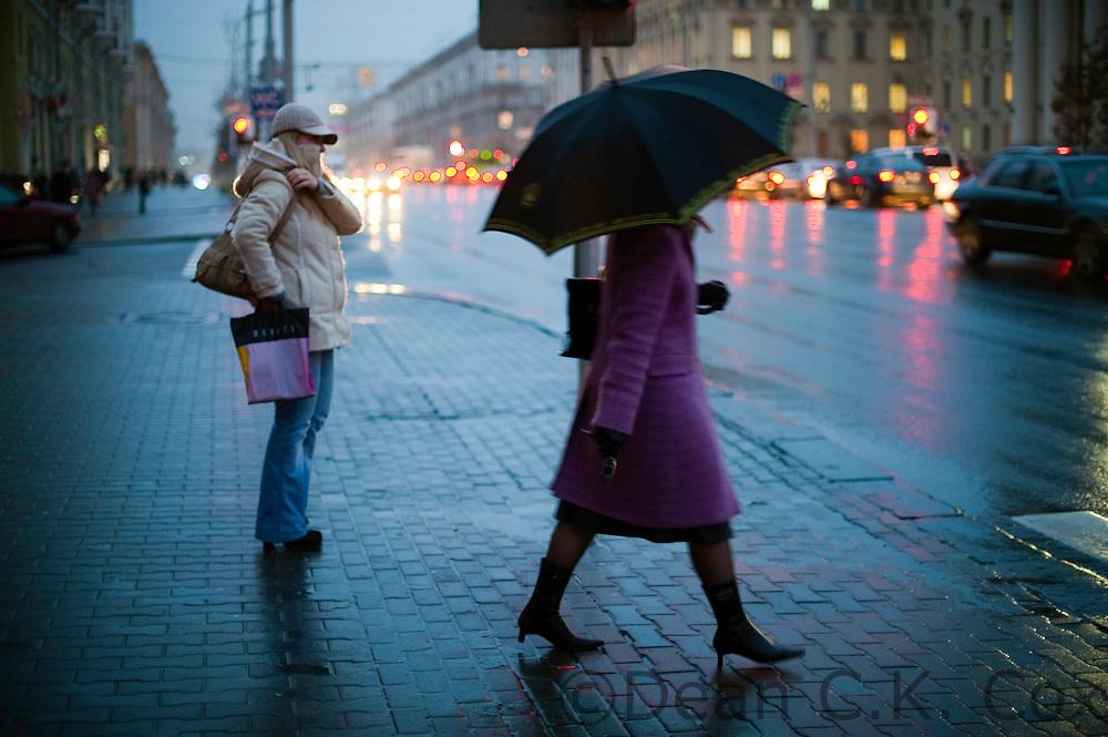 Under a light rain, pedestrians wait to cross the main road through downtown Minsk on Oct. 22, 2009.