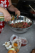 Cooking Moroccan meatballs in tomato sauce adding oil to the minced meat