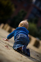A toddler boy crawls and explores water and his world.