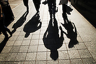 The shadows of two people holsing hands are cast on Lake Street in Chicago.