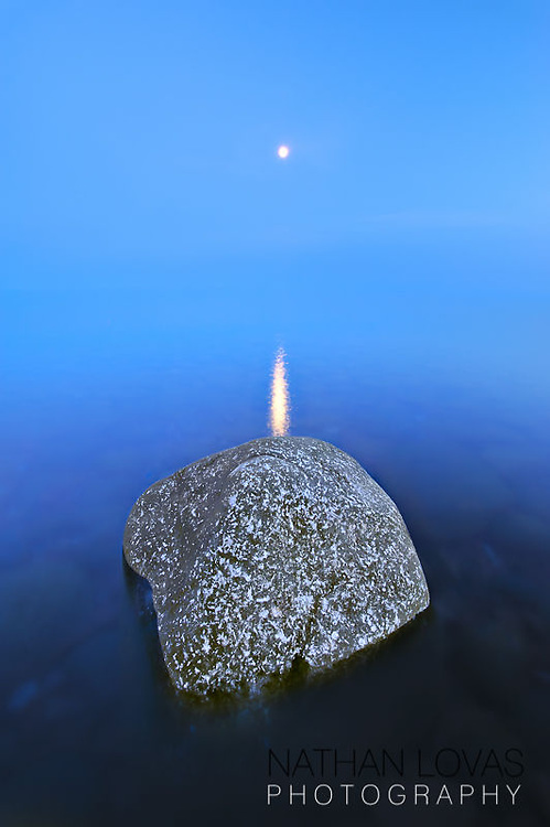 Moonrise over Lake Superior with blue water and large rock;  North Shore, Minnesota.