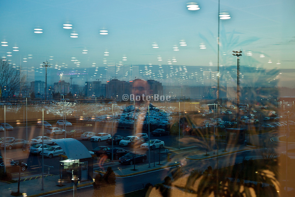 male person reflecting in window with outside a large car parking at Ataturk airport Istanbul Turkey at sunrise