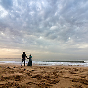 Couple walking at Sunset in Dar Bouazza beach, in Tamarist, Casablanca. Morocco.