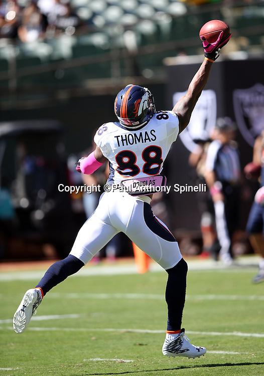 Denver Broncos wide receiver Demaryius Thomas (88) jumps and catches a pregame pass with one hand while warming up before the 2015 NFL week 5 regular season football game against the Oakland Raiders on Sunday, Oct. 11, 2015 in Oakland, Calif. The Broncos won the game 16-10. (©Paul Anthony Spinelli)