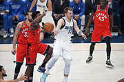 Dallas Mavericks point guard Luka Doncic (77) completes the no-look pass against the Raptors while being guarded by Toronto Raptors shooting forward OG Anunoby (3), Pascal Siakam (43) and Marc Gasol (33) during an NBA basketball game, Saturday, Nov. 16, 2019, in Dallas. The Mavericks defeated the Raptors 110-102. (Wayne Gooden/Image of Sport)