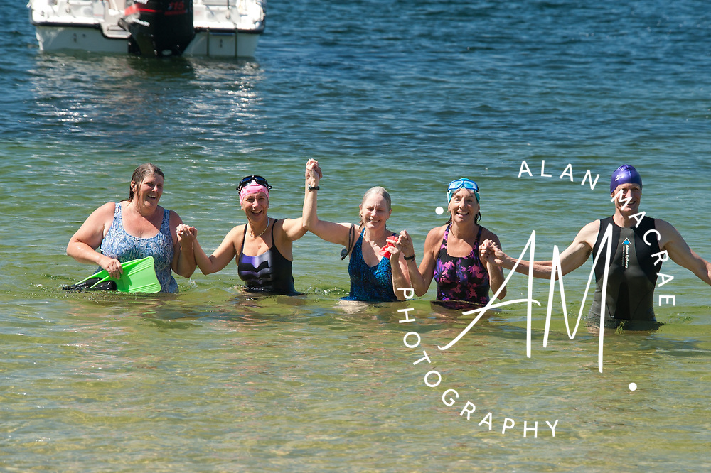 Nancy Jones Hansen, Wendy Vandepull, Blair Newcomb, Rosemarie DeMars and Rick Vandepull celebrate as the exit Squam Lake at the Sandwich town beach following a seven mile trans lake swim on Thursday, August 19, 2010.  (Alan MacRae/for the Citizen)