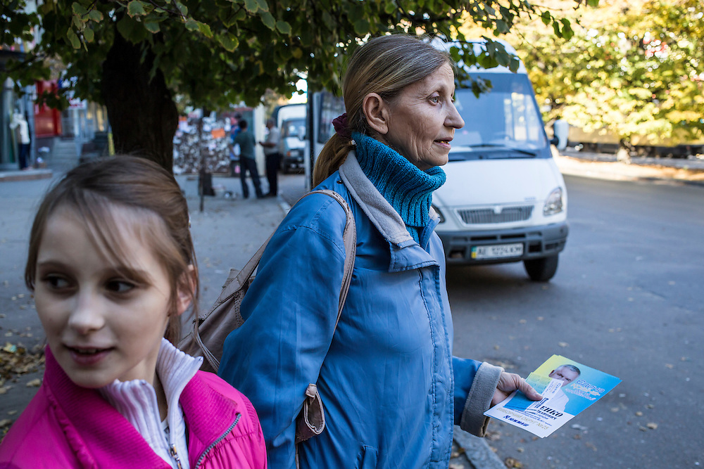 DNIPROPETROVSK, UKRAINE - OCTOBER 12: Yeva, 10, and her grandmother, Svitlana Kostromina, wait for a bus on the long trip from the Good News Evangelical Church to the home where they are living with a family that is part of the congregation on October 12, 2014 in Dnipropetrovsk, Ukraine. Yeva and her family fled fighting in Luhansk; the minibus behind them would be a quicker way back but they can't afford it. The United Nations has registered more than 360,000 people who have been forced to leave their homes due to fighting in the East, though the true number is believed to be much higher.(Photo by Brendan Hoffman/Getty Images) *** Local Caption *** Svitlana Kostromina
