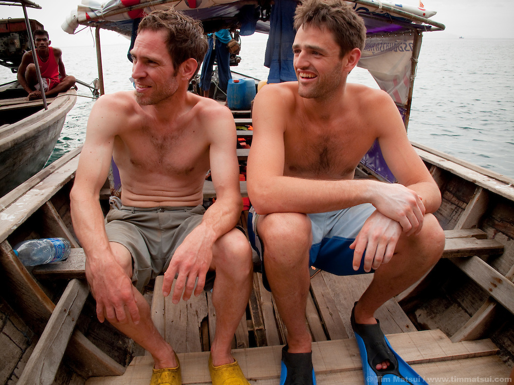 Two caucasian male tourists go snorkeling from a longtail boat near Tonsai, Thailand.