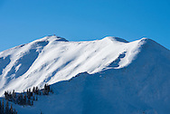 Skiers hike the ridge to access Highland Bowl at Aspen Highlands in Aspen, Colorado.