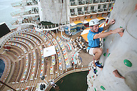 The launch of Royal Caribbean International's Oasis of the Seas, the worlds largest cruise ship..A guest on the rock climbing wall with the aqua theater in the background.