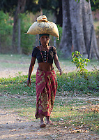 Nepali woman carrying a bag on her head, Bardiya, Nepal