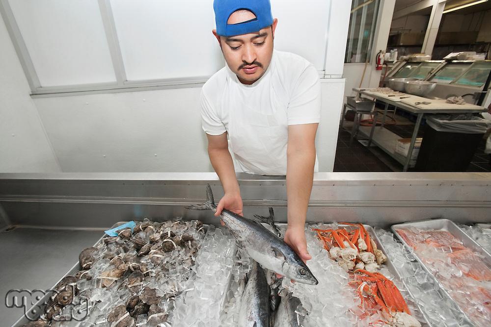 Young fishmonger holding up mackerel amidst mixed fish on ice at fish market