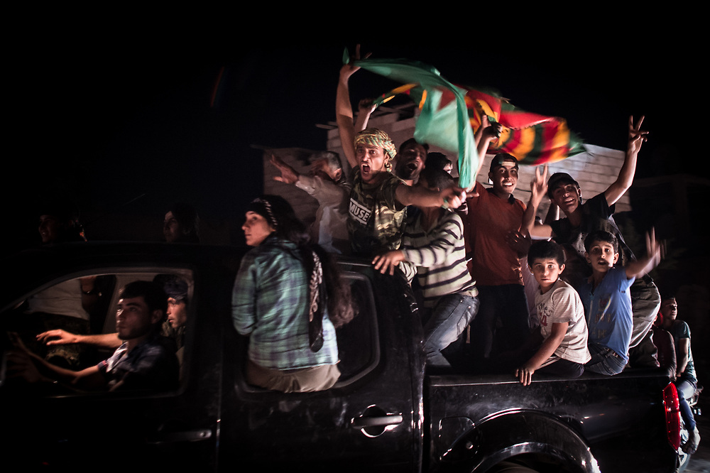 "In the streets of Kobane, people are celebrating the capture of the city of Tell Abyad by the ""People's Defense Units"" / "" Women's Defense Units"" (YPG / YPJ) and their allies. The recapture of the territory that had been taken by""Islamic State"" (ISIS) connects the cantons of Kurdish self-administration of Kobane and Jazira.  Kobanê (Ayn al-Arab), Syria, June 15, 2015"