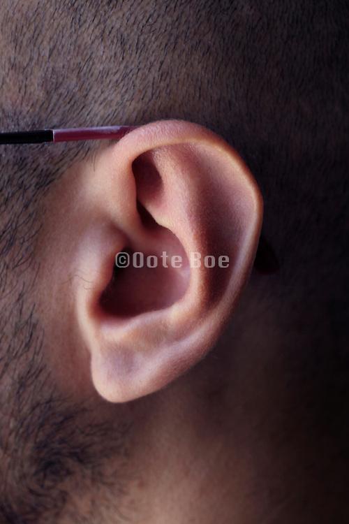 ear of man wearing glasses