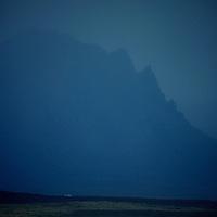 Sea, surf, farm & land, & massive mountain silhouette in background mist.