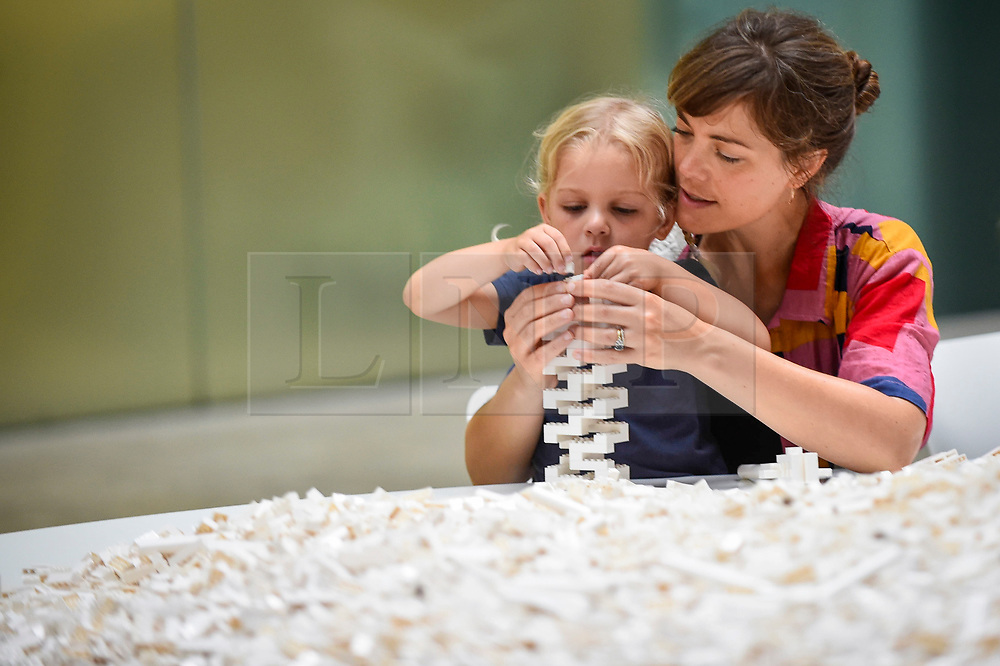 "© Licensed to London News Pictures. 26/07/2019. LONDON, UK. Margot Cartwright-Naylor, aged 4, and her mother work with Lego at the preview of ""The cubic structural evolution project"", 2004, by Olafur Eliasson at Tate Modern.  Exhibited for the first time in the UK, the artwork comprises one tonne of white Lego bricks inspiring visitors to create their own architectural vision for a future city and is on display until 18 August 2019.  The work coincides with the artist's new retrospective exhibition ""In real life"" at Tate Modern on display to 5 January 2020.  Photo credit: Stephen Chung/LNP"