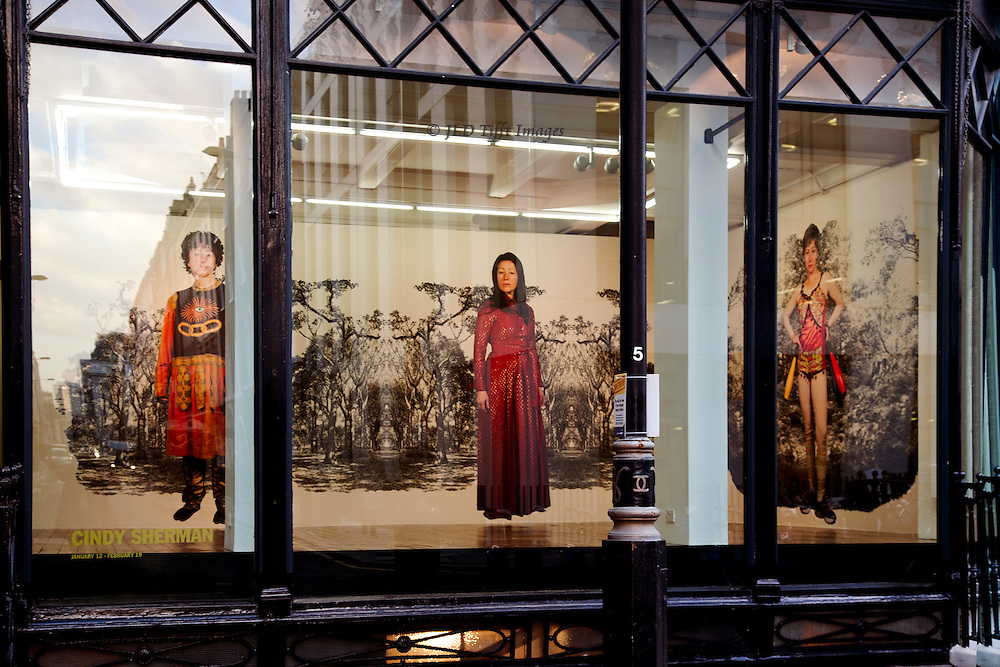 Through the display window of the gallery of Monika Spruth and Philomene Magers, London, during a show of new photos by Cindy Sherman, whose figure is seen in over life size enlargement on the walls.  They are so placed in a black-and-white background landscape that the three standing figures, each in a different costume, seem to float. I have admired Sherman's work and went specifically to look at this show.  It was to me more like a performance than an exhibition of work one might want to own.  Nevertheless an interesting view at dusk.  The street behind is reflected faintly in the windows too.