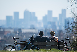 © Licensed to London News Pictures. 05/04/2020. London, UK. Members of the public sitting on a park bench, overlooking the city of London from Parliament Hill on Hampstead Heath, London, during a pandemic outbreak of the Coronavirus COVID-19 disease. The public have been told they can only leave their homes when absolutely essential, in an attempt to fight the spread of coronavirus COVID-19 disease. Photo credit: Ben Cawthra/LNP