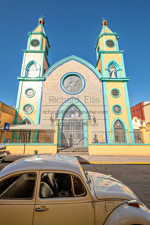 An old Volkswagen Beetle parked outside the colorful Our Lady of Fatima Church in the central historic district of Coatepec, Veracruz State, Mexico.