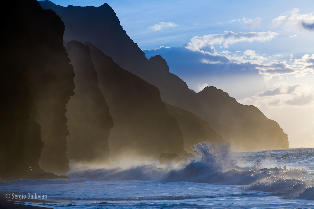 The fluted ridges of the Na Pali Coast rise above the crashing surf on the north shore of Kauai, Hawaii.  The ridges are the result of volcanic rock that has been eroded over time by weather patterns of rain, wind and ocean waves.