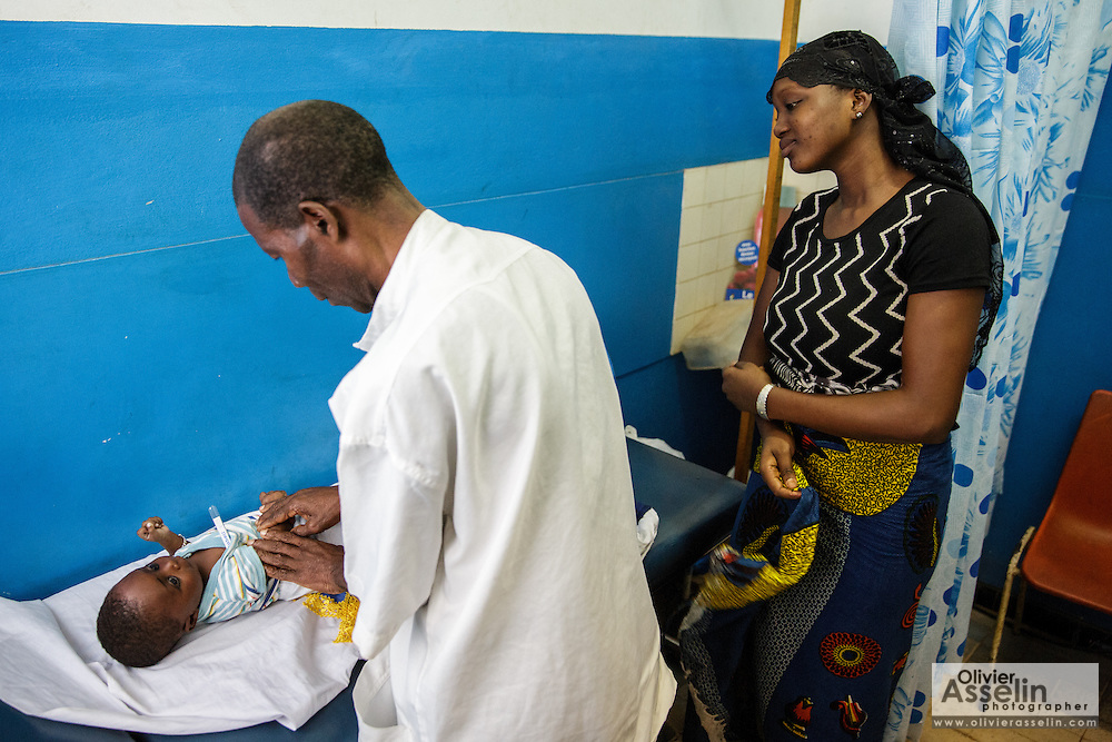 A nurse examines a child while his mother watches at the Libreville health center in Man, Cote d'Ivoire on Wednesday July 24, 2013.