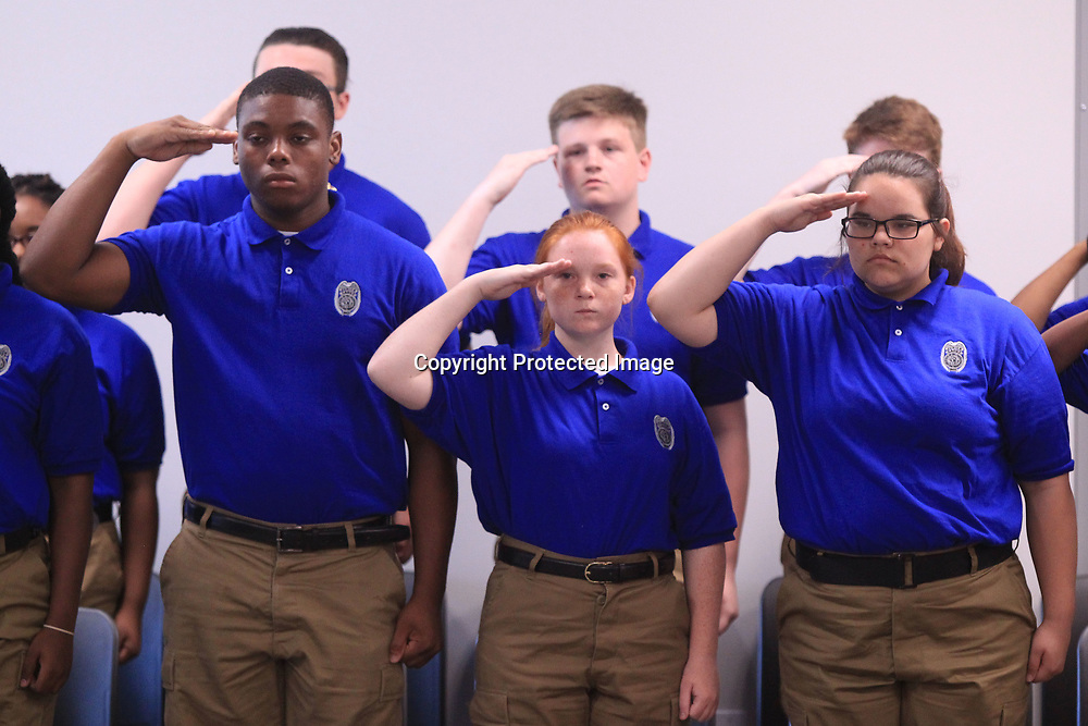 Graduating cadets from the Tupelo Police Department's Junior Police Academy, salute the flag during the Pledge of Allegiance at their commencement ceremony in Tupelo Friday morning.