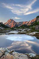 Partially thawed tarn, Yellow Aster Butte Basin. American Border Peak and Yellow Aster Butte are in the distance. Mount Baker Wilderness, North Cascades Washington